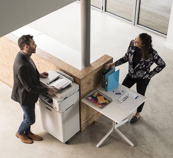 kobieta i mężczyzna stoją w biurze przy drukarce i rozmawiają