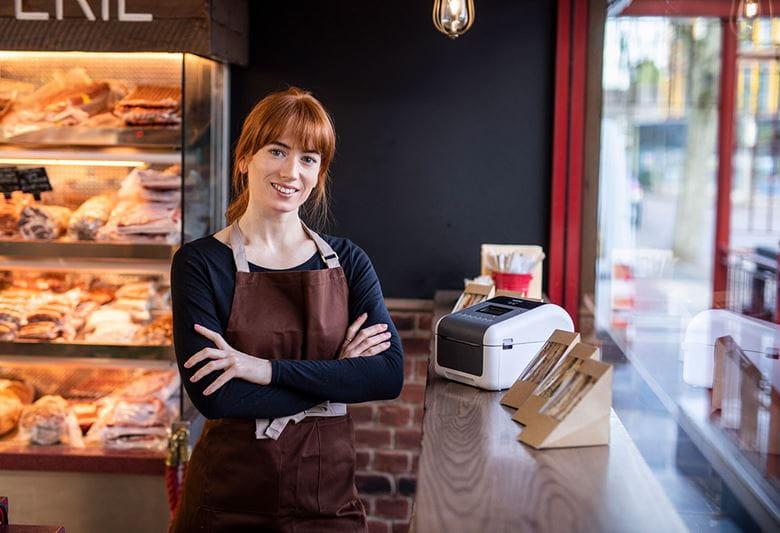 Žena okrenuta prema kameri, prekriženih ruku, stoji u delikatesi, na pultu pored sendviča stoji Brother TD pisač naljepnica