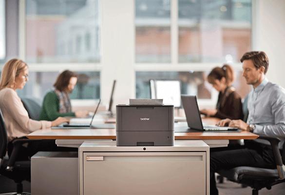 laserowa drukarka Brother stoi na biurku, z tyłu widać pracujących ludzi