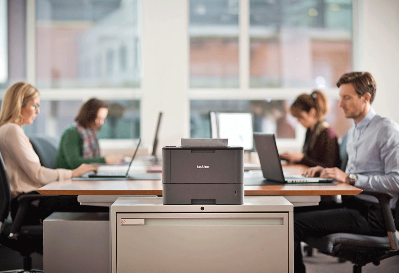 laserski tiskalnik Brother na mizi, v ozadju osebje