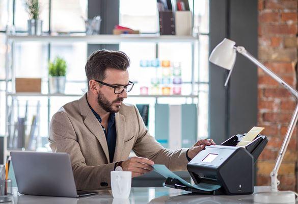 skaner Brother stoi na biurku, ma dokumenty na podajnikach, z tyłu widać mężczyznę w okularach oraz laptopa