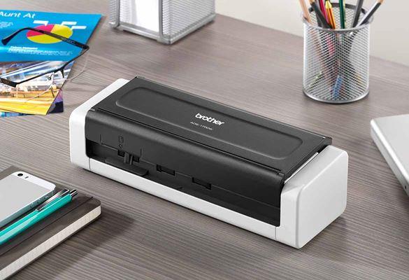 zaprt kompaktni dokumentni skener Brother ADS-1700W na sivi mizi