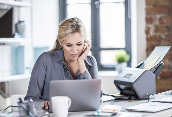 Ženska z dolgimi svetlimi lasmi sedi za mizo s prenosnikom in namiznim skenerjem Brother ADS-3600W, skodelica, pisalo in beležka