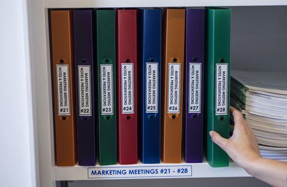 Teczki na dokumenty stoją na półce, są wyraźnie oznaczone przy użyciu trwałej etykiety Brother P-touch