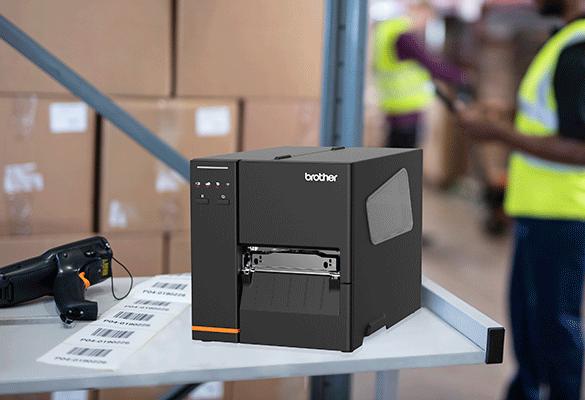 Imprimanta TJ-4020TN pe un banc de lucru alaturi de un scaner si niste etichete intr-un depozit