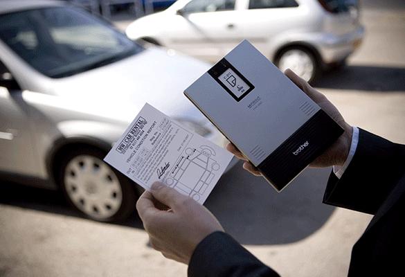 Tiskalnik MW v roki moškega, ki stoji ob avtomobilu in drži natisnjen obrazec A6
