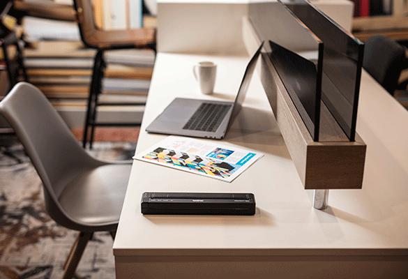 drukarka Brother PJ lezy na biurku, obok srebrny laptop i wydrukowana kartka