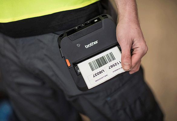 urządzenie RJ-4 drukuje etykietę, mężczyzna ubrany w czarne spodnie ma drukarkę przy pasku