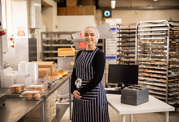 Ženska v predpasniku in mreži za lase v industrijski kuhinji ob tiskalniku Brother TD-4T