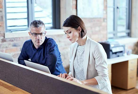 Mężczyzna i kobieta pracujący na komputerach w biurze