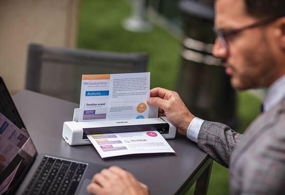 Muškarac s naočalama, u sivom odijelu i s laptopom sjedi za sivim stolom na otvorenom i mobilnim skenerom skenira dokument u boji