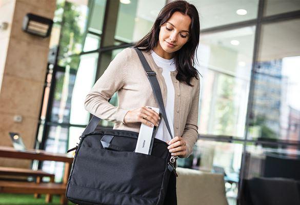 Жена поставя мобилен скенер в чанта за лаптоп, дървена маса, стъклен прозорец