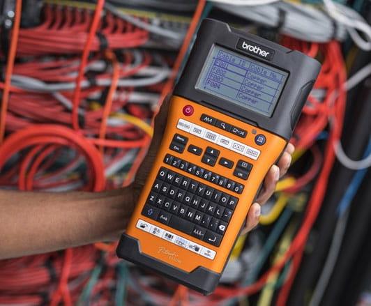 A Brother PT-E550WNIVP professzionális hálózati azonosító címkenyomtató készletet egy hálózati telepítő kezében tartja