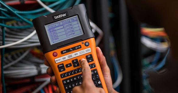A nyomtatáshoz hálózati kábel-azonosítóval ellátott PT-E550W címkenyomtatót választanak