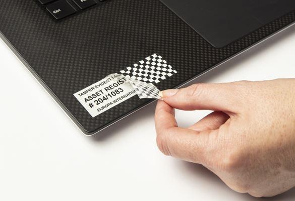 Persoană care scoate o bandă de securitate de pe un laptop, iar eticheta lasă o amprentă hașurată
