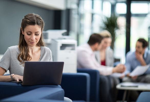 Žena sjedi na kauču i koristi prijenosno računalo, u pozadini ljudi na sastanku