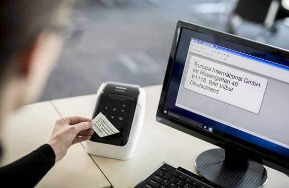Pracownik biurowy wyjmuje wydrukowaną etykietę ze swojej drukarki etykiet QL