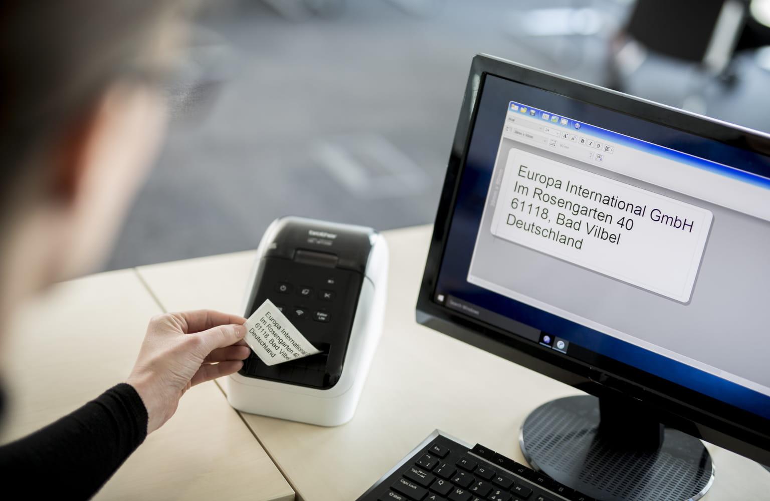 Pisarniški delavec odstrani natisnjeno nalepko s tiskalnika nalepk QL