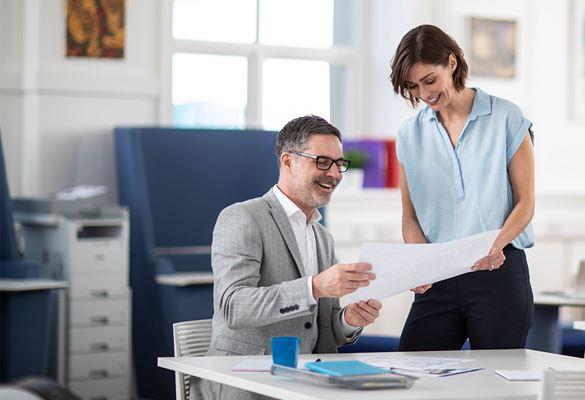 Мъж и жена в офиса обсъждат документ, зад тях монохромен лазерен принтер с допълнителни тави