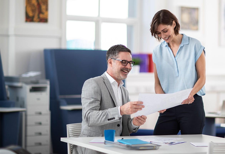 Moški in ženska v pisarni razpravljata o dokumentu, črno-beli laserski tiskalnik na pladnjih v stolpu pnem predalu v ozadju