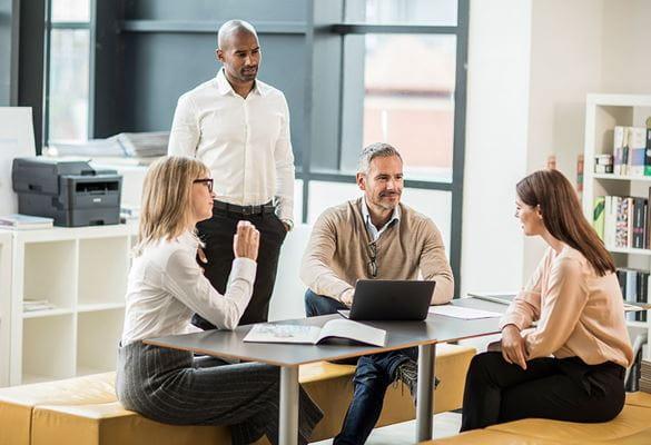Skupina ljudi v pisarni s črno-belim laserskim tiskalnikom v ozadju