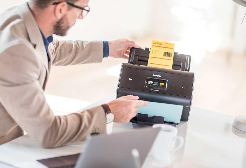 Moški z očali sedi za mizo in skenira dokument z Barcode Utility