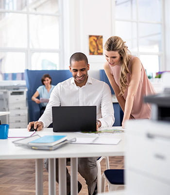 Kobieta w okularach stoi nad mężczyzną i razem patrzą na ekran monitora, drukarki,  komputery, papier