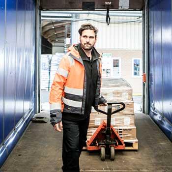 Moški v oranžnem opozorilnem jopiču vleče ročnega viličarja s škatlami v tovornjaku z modrimi stranicami