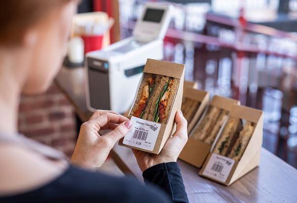 Žena v kavárně lepí štítek na sendvič
