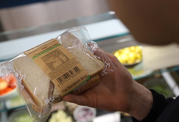 Osoba trzyma kanapkę zapakowaną w przezroczystą plastikową folię z brązową etykietą ze składnikami