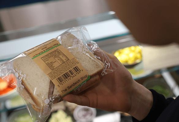 Persoană care ține sandvișul într-o pungă de plastic transparentă, cu o etichetă maro cu ingrediente