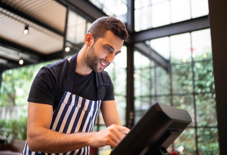 Číšník s černou košilí a pruhovanou zástěrou zpracovává účtenku na dotykovém displeji