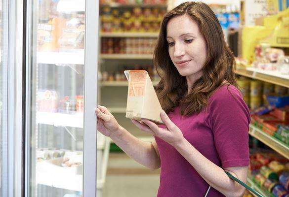 Ženska z rjavimi lasmi do ramen v vijolični majici drži vrata hladilnika in gleda sendvič