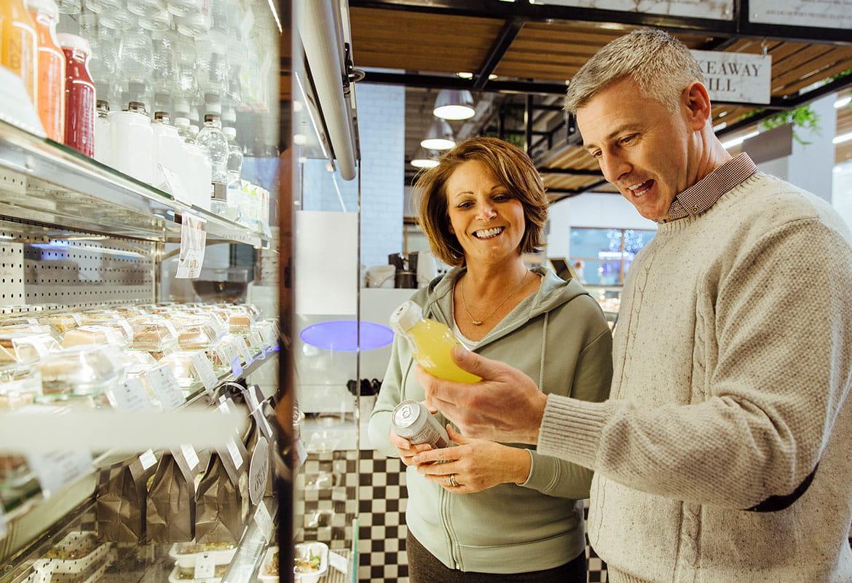 Muž a žena stojí před chladicí skříní a porovnávají balené nápoje v kavárně