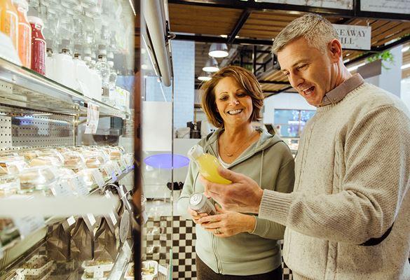 Bărbat și femeie stând în fața raftului frigorific, comparând băuturile îmbuteliate dintr-o cafenea