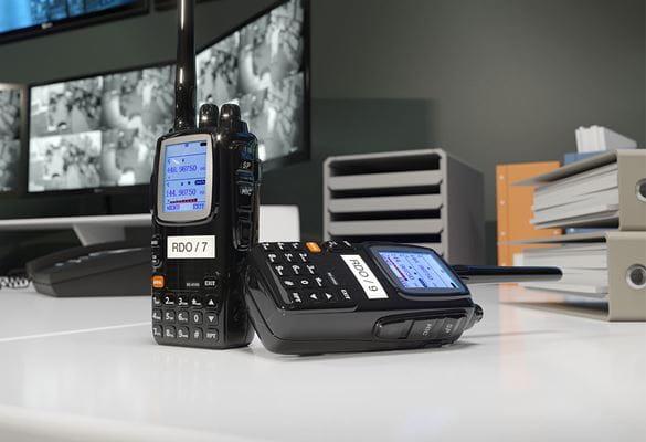Vysílačka na stole s identifikačním štítkem, monitory a šanony v pozadí