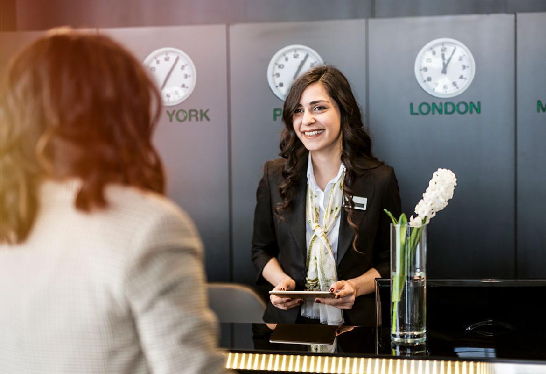 Hotelový host na recepci s recepční, hodiny, počítač, váza