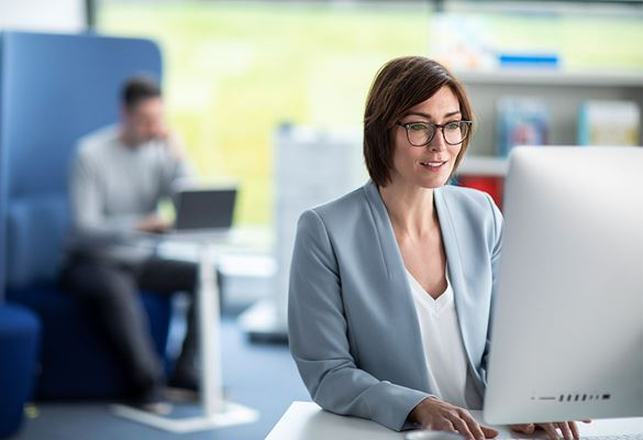 Nő visel szemüveget,  számítógépen dolgozik az irodában, nyomtató és egy férfi a háttérben