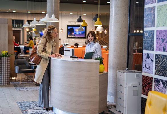 Recepcionarka s gošćom na recepciji; pisač, svjetla, restaurant, cvijeće, stolica