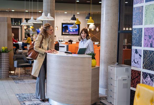 Receptorka z gostjo na recepciji; tiskalnik, luči, restavracija, cvetje, stol