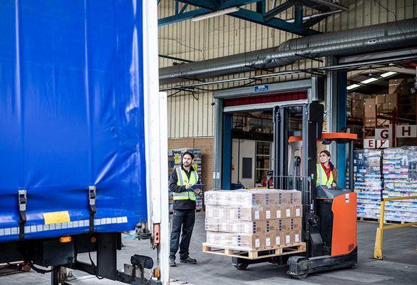 Ženska vozi viličar s paleto, tovornjak pred skladiščem in distribucijskim centrom, moški v opozorilnem jopiču drži seznam