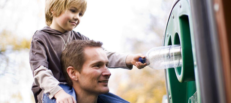 Muškarci drže dijete na ramenima i zajedno recikliraju plastičnu bocu