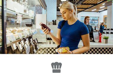 Ženska s spetimi svetlimi lasmi v modri majici v trgovini gleda v steklenico soka in drži sendvič