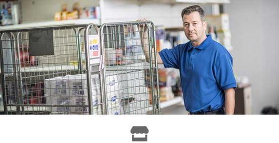 Férfi kék pólóban fém ketrecen támaszkodik egy boltban