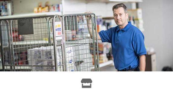 Bărbat în tricou albastru care se ține de cușca metalică dintr-un magazin