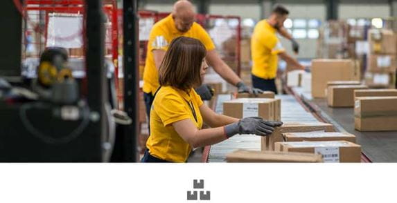 Ženska in dva moška v rumenih polo majicah, ki delajo v skladišču, za tekočim trakom s škatlami