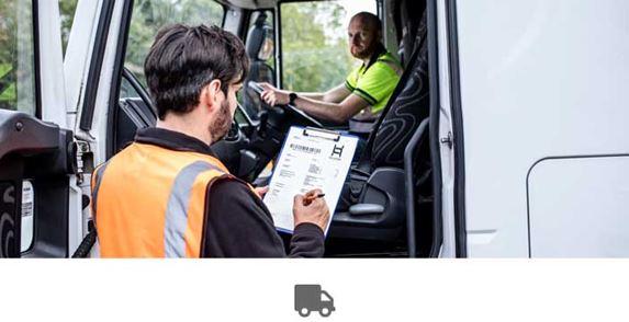 Az ember teherautóban ül, nyitva az ajtó, narancssárga mellényes férfi jegyzetet tart a kezében és ír rá
