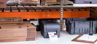 Imprimantă de etichete gri Brother pe birou, cutii maro, clipboard, ladă gri, rafturi portocalii