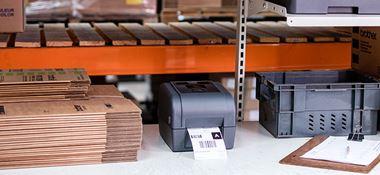 Šedá tiskárna štítků Brother na stole, hnědé krabice, schránka, šedá přepravka, oranžové police