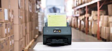 Scanner de birou Brother ADS-3600W pe masă în depozit cu cutii pe rafturi